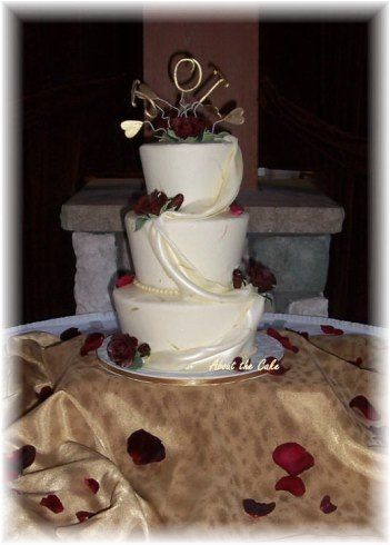 Elegance meets funky.  This 3 tiered wedding cake features tapered buttercream iced cakes with...