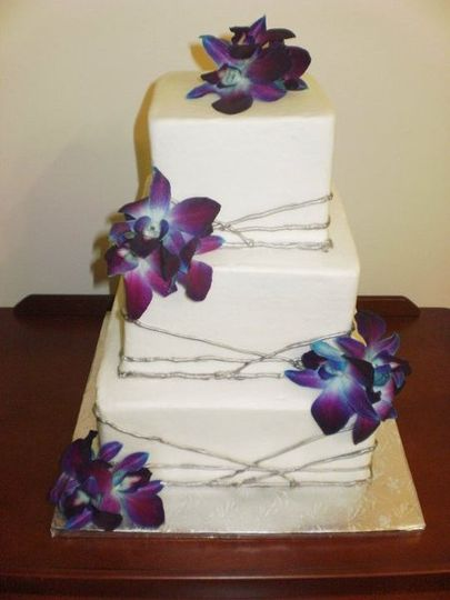 3-tier square cakes finished in white buttercream with silver striping.  Fresh purple dendrobium...