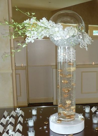 White orchids and suspended floating gold nuggets in tall cylinder with uplight.