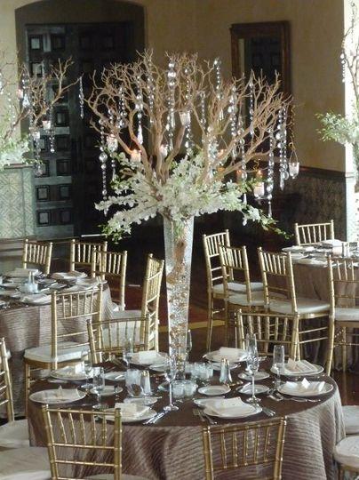 Manzanita, orchids, and dangling crystals create drama in a dark ballroom.