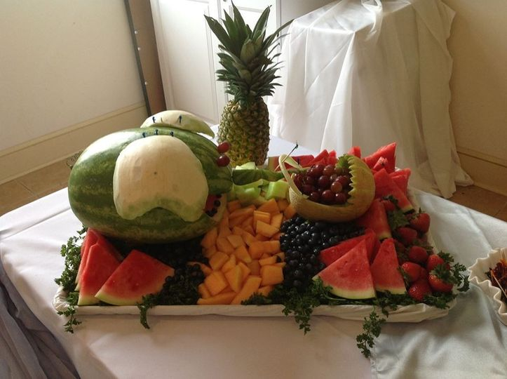 Watermelon carved to be elephant pushing a baby buggy for the elephant theme baby shower