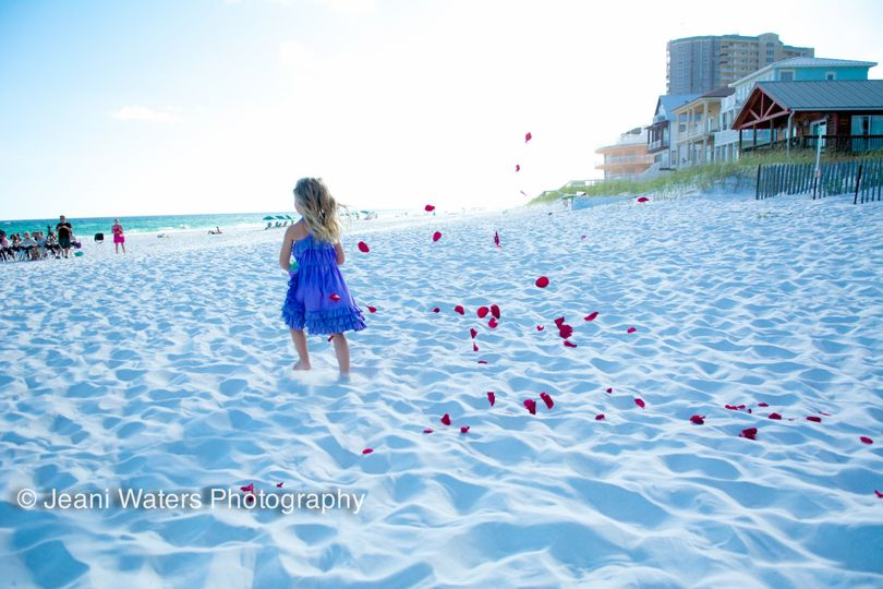 Flower girl captured by our photographer Jeani Waters as she breezes down the beach in front of the...