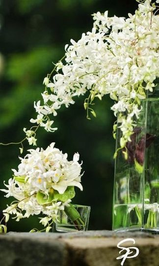 Sprays of white dendrobium orchids, iris, Casablanca Oriental Lilly.   Floral Design by: Art of...