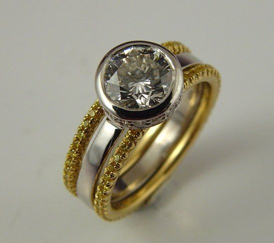 Round brilliant cut diamond in platinum with fancy yellow diamonds in yellow gold.