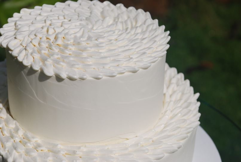 Chrysanthemum topped wedding cake with smooth finish sides.