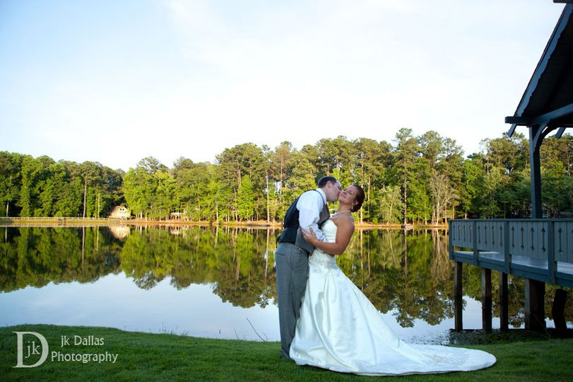 Groom kissing his bride by the lake