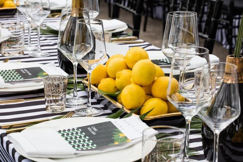 Table setting with black and white stripe linen, Arezzo Gold Flatware, and white classic china