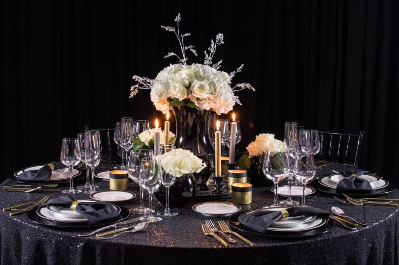 Table setting with black acrylic charger, Lillyana china, Riedel Glassware, and a combination of the...