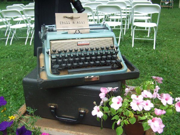 A Vintage Typewriter holds the Typed Program for the Ceremony, and is sitting atop a stack of old...