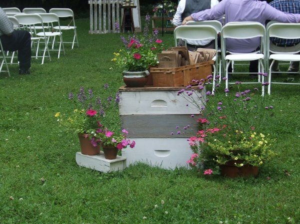 A Stack of Bee-Keeping Boxes topped with a vintage basket  hold the programs for this Outdoor...
