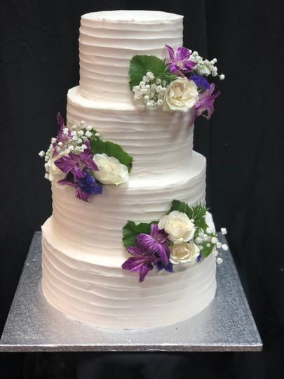 Four tier wedding cake with purple and white flowers