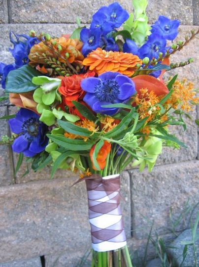 a vibrant summer wildflower bouquet with blue anemone, delphinium, orange zinnias and chartreuse...