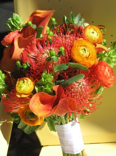 vibrant summer bouquet with pincushion protea, mango calla lilies, and orange ranunculus with...