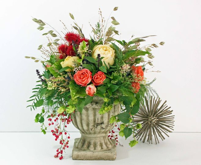 A beautiful garden urn, filled with garden roses, berries and textured greens.