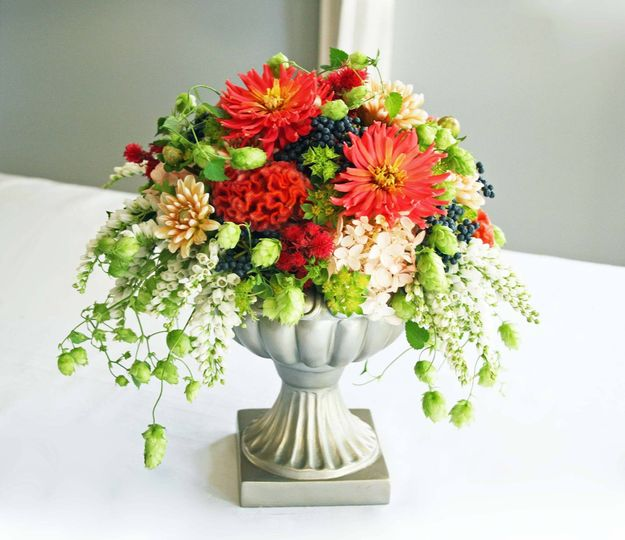 Dahlias, Hops, Viburnum berry and Japanese Pieris make for a lovely, bright combination in this...