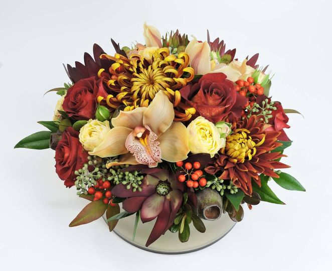 Orchids, roses, chrysanthemum, berries and autumnal foliage went into this gorgeous centerpiece.