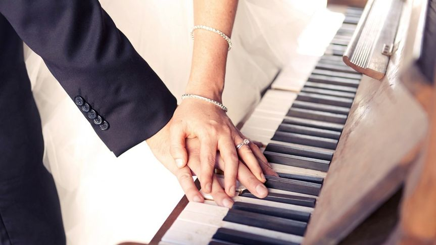 Couple holding hands by the piano