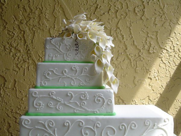 Hand crafted calla lily's cascade over this elegant fondant cake. Alternating tiers of vanilla cake...