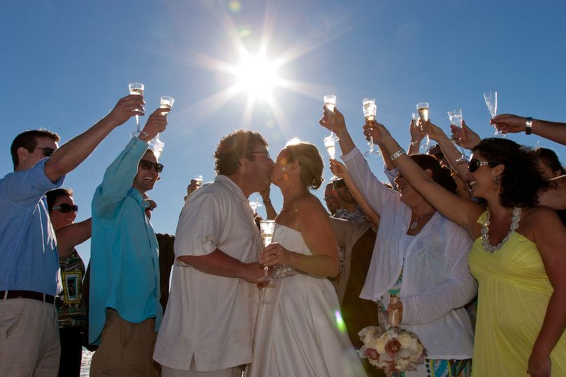 bride and groom toast to their new life together with family and friends at a Captiva Island beach...