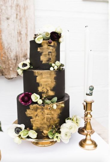 Black and gold themed cake with flower decorations