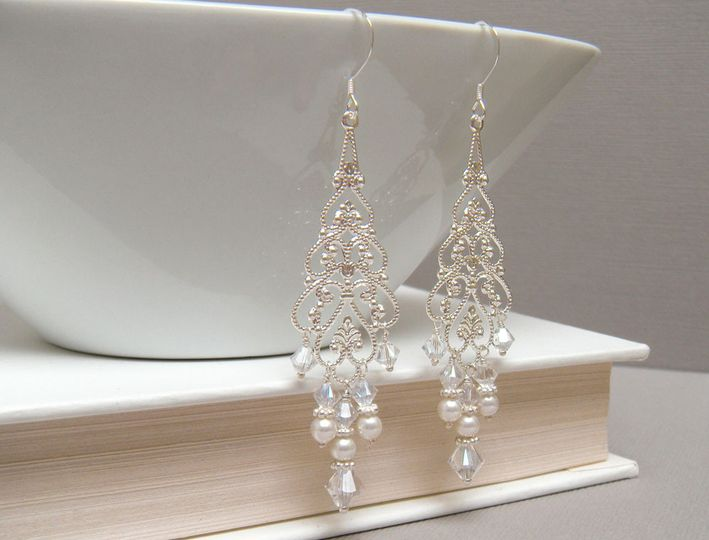 The Juliet Chandelier Earrings are created from silver plated filigree and adorned with ivory or...