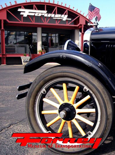 front of museum with model t wheel with logo