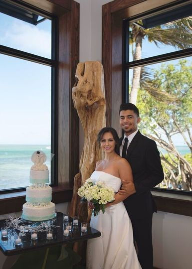Newlyweds by the wedding cake table