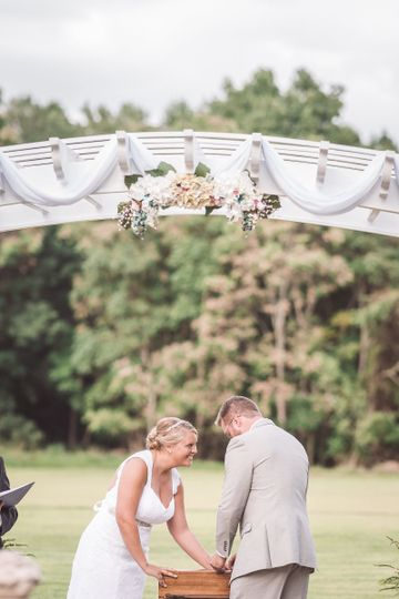 Photo by Sharon Elizabeth Photography  Bride and Groom sealing their time capsule in their outdoor...