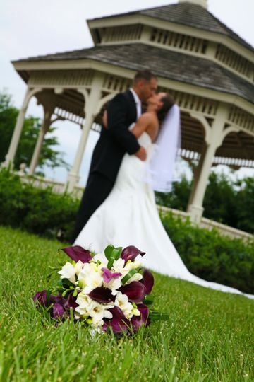 Couple kiss with bouquet in foreground