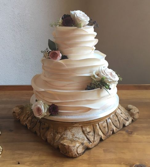 White wedding cake on a log