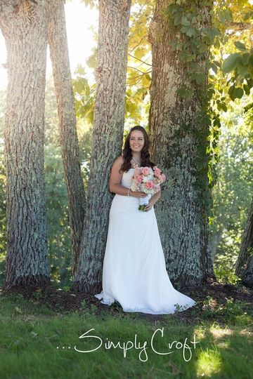 Bride at tree stand located near the log farmhouse
