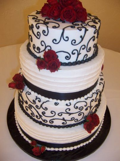 Fresh red roses compliment the white banding and black scroll work of this cake