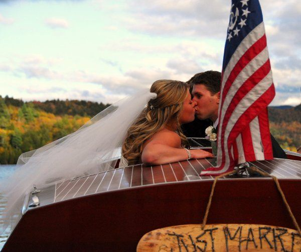 Newlyweds kissing by the flag