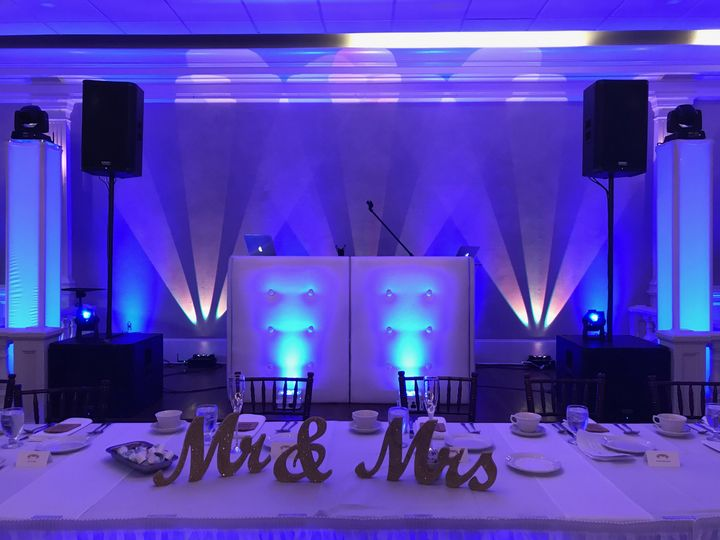 White dj facade with blue accent wall & gold tri-beams