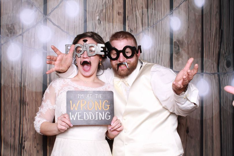 Bride & groom photo booth with rustic backdrop