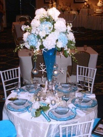 Tall glass vase (rental) with tiffany blue gell and lights. Large arrangement on top of hydrangea,...