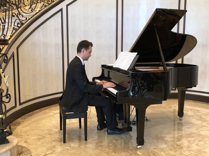 Mikhail in a classic tux playing the grand piano
