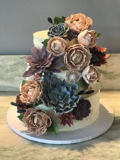 Peonies, succulents, and anemones on wedding cake