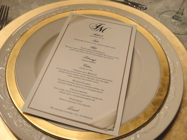 Custom gold and black wedding menu printed on linen paper and accented with ribbon corners.