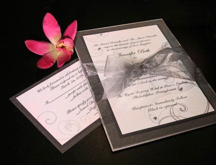 Custom wedding invitation in white and charcoal with swirl design and silver ball accents. Tied with...