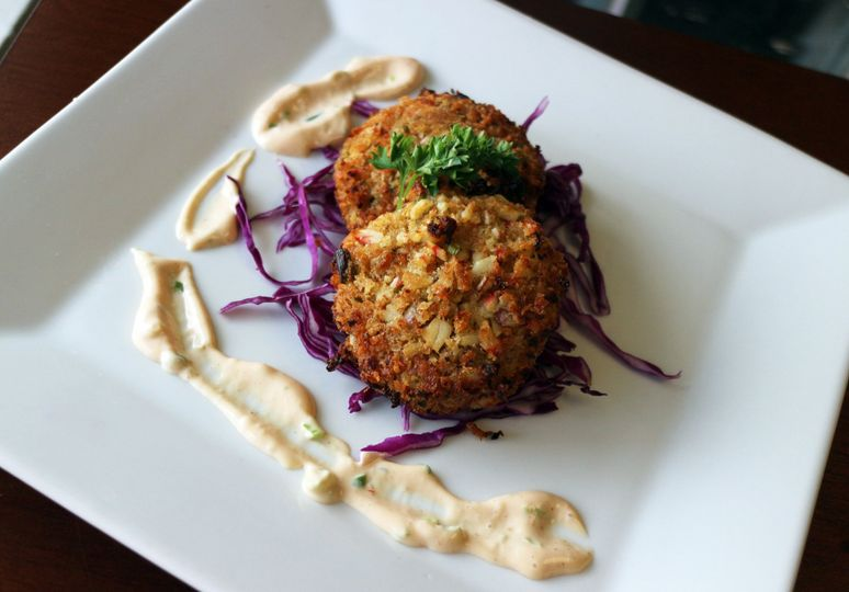 Crab cakes with a sweet red cabbage garnish.