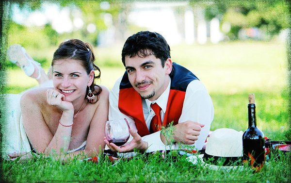 A couple having picnic in a field. This is a Gypsy themed wedding.