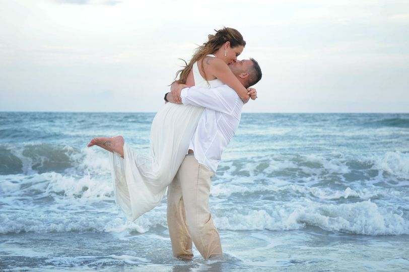 Newlyweds kiss on the shore