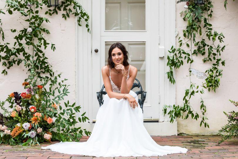 Bride sits on stoop w/ flowers