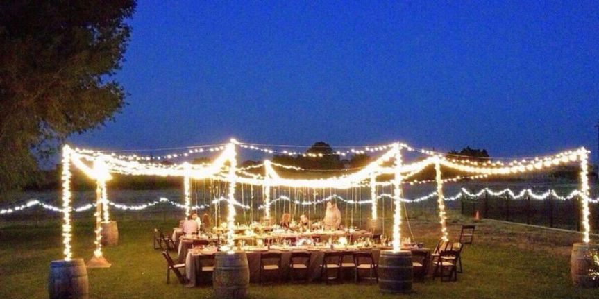 Our rustic wine barrels with canopy lighting for a backyard wedding reception.