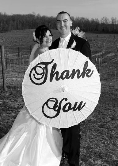 Bride and groom holding a thank you sign