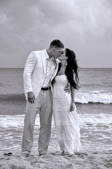 Groom kissing his bride at Oak Island NC. Ocean in background. Monochrome. Billy Beach.