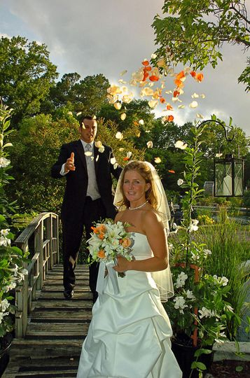 Bride looking at camera with groom throwing flower petals over her at the Arboretum in Wilmington,...