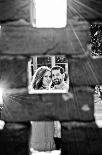 Couple looking through a brick wall in downtown Wilmington, NC. Monochrome. Billy Beach.