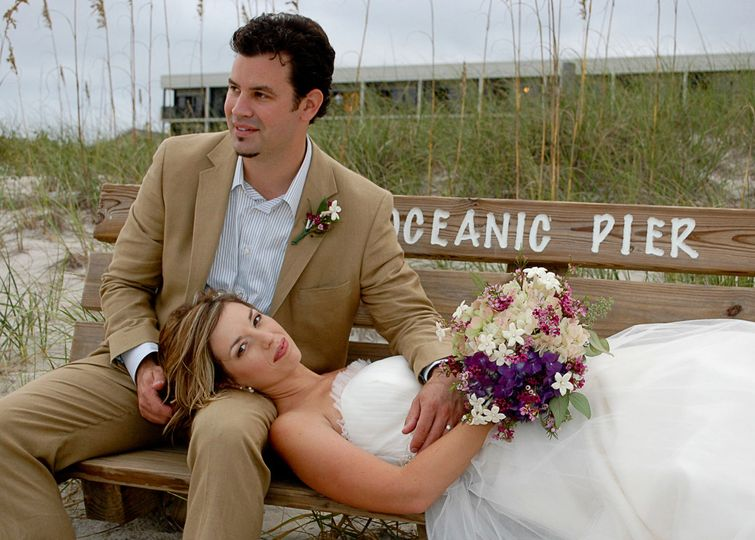 Bride and groom resting on bench near Oceanic at Wrightsville Beach, NC. Billy Beach.